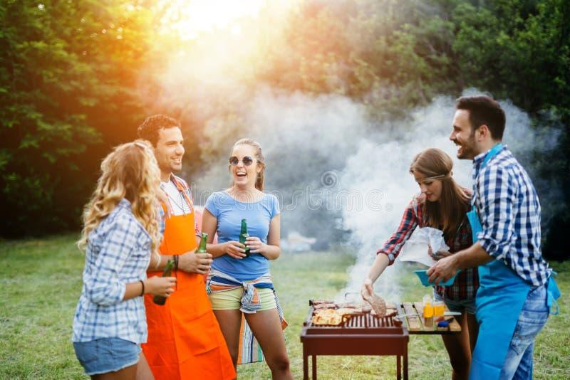 Vänner som har ett grillfestparti i natur royaltyfri fotografi