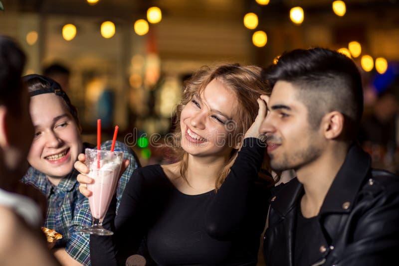 Vänner som har ett kaffe tillsammans kvinnor och man på kafét och att tala som skrattar royaltyfri fotografi