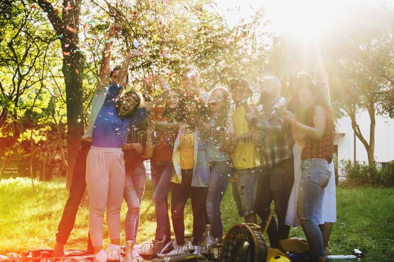 Vänner som har ett parti parkerar in, utanför att blåsa konfettier royaltyfria foton