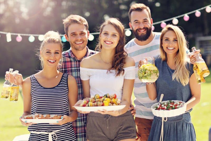 Vänner som har grillfestpartiet i trädgård royaltyfria bilder