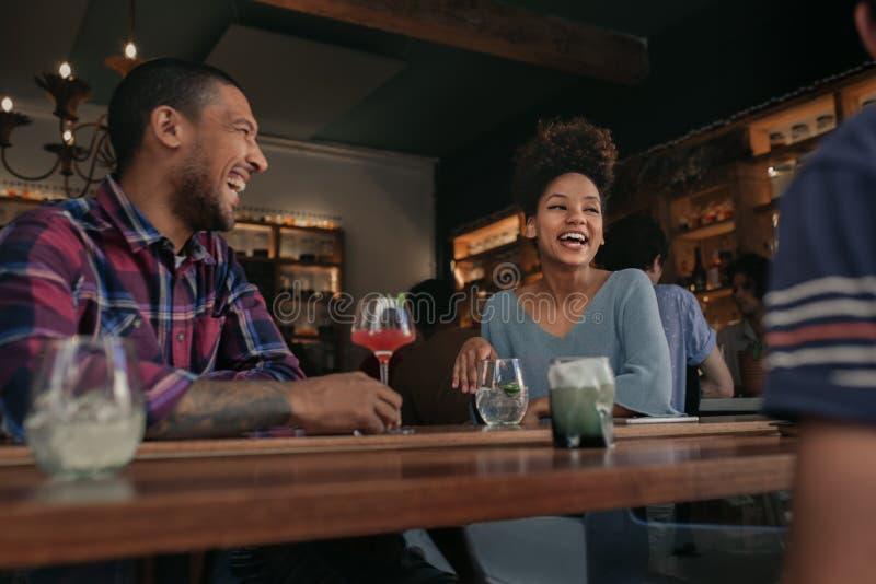 Vänner som har gyckel över drinkar tillsammans i en stång royaltyfri foto
