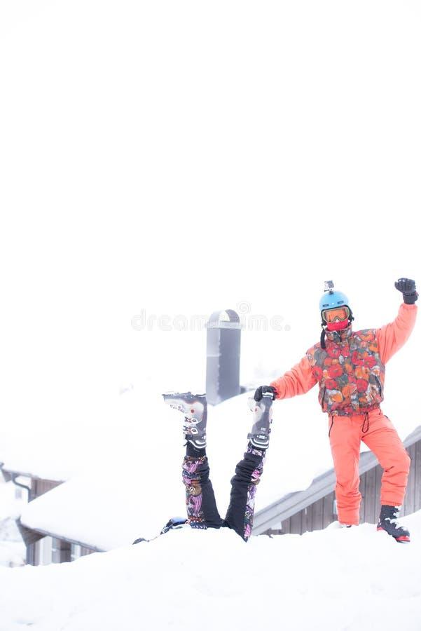 Vänner som har gyckel överst av berget, medan skida/snowboarding royaltyfri bild