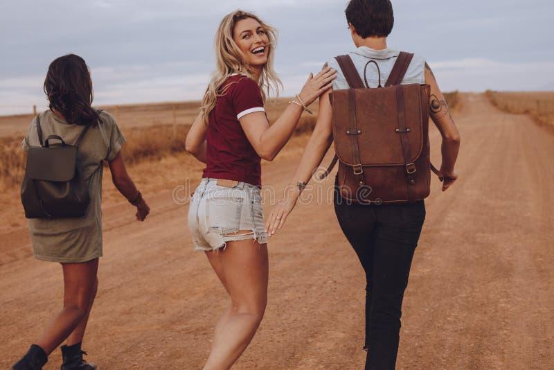 Vänner som har gyckel som går på landsvägen royaltyfri bild