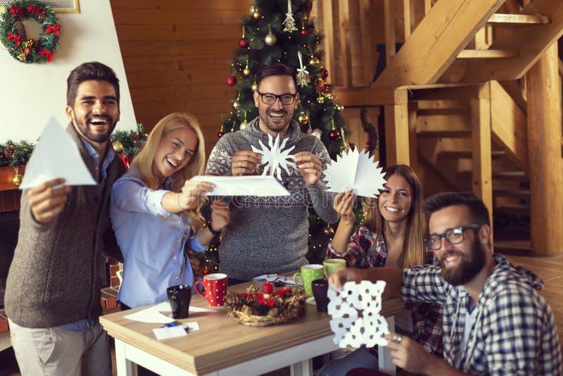 Vänner som har gyckel som gör julpynt arkivfoton