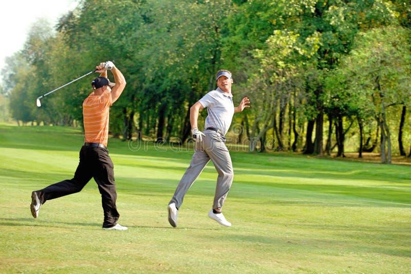 Vänner som har gyckel i golfbana arkivfoton