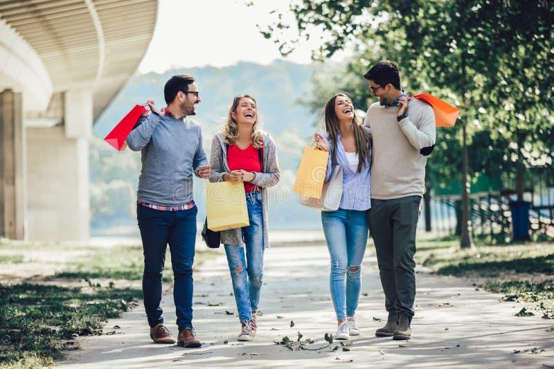 Vänner som har gyckel i shopping och att rymma shoppingpåsar och kreditkorten royaltyfria foton