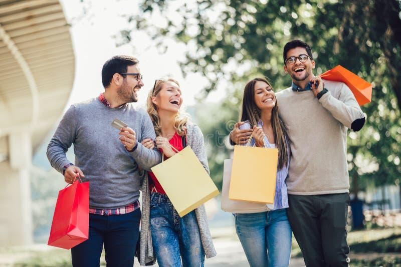 Vänner som har gyckel i shopping som rymmer den shoppingpåsar och kreditkorten royaltyfri bild