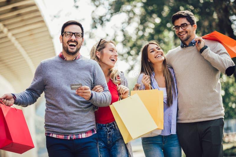 Vänner som har gyckel i shopping som rymmer den shoppingpåsar och kreditkorten royaltyfria foton