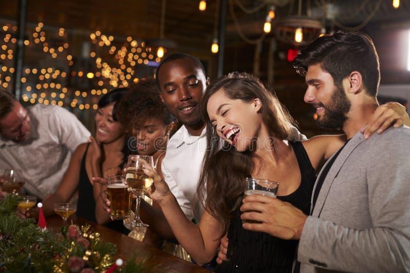 Vänner som har gyckel på ett julparti i en stång arkivfoto