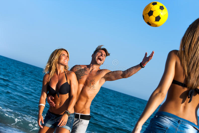 Vänner som har gyckel på strand med bollen. royaltyfria bilder
