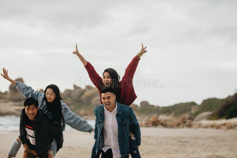 Vänner som har gyckel på strandsemester royaltyfria bilder
