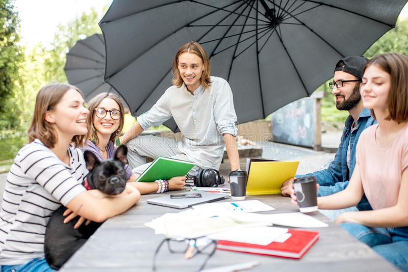 Vänner som har gyckel tillsammans under en studie utomhus arkivfoto