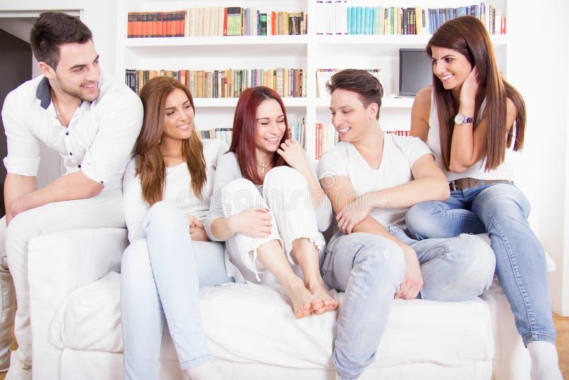 Vänner som har konversation på soffan hemma fotografering för bildbyråer