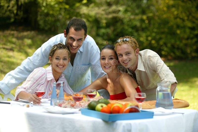 vänner som har lunch utanför royaltyfri fotografi