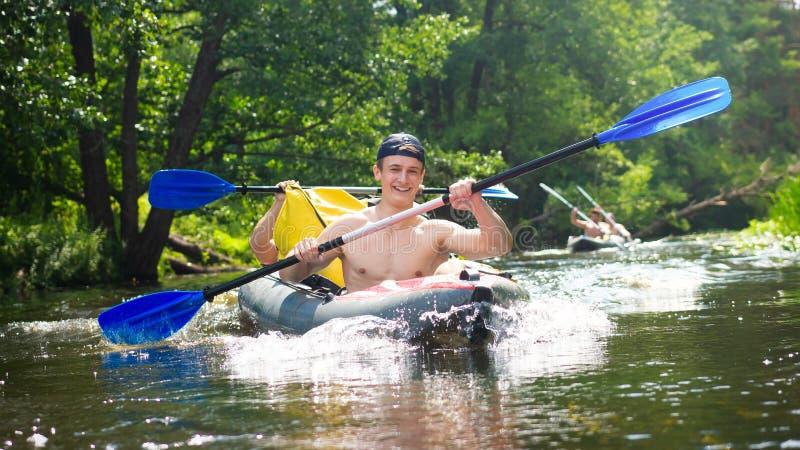 Vänner som har lycka under rafting på floden Grabbar i kanot med skovlar Rodd i fartyg på helgen royaltyfri foto