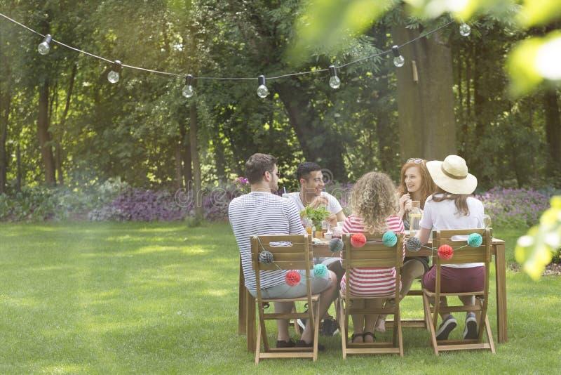 Vänner som har matställen i trädgården under sommartid arkivfoto