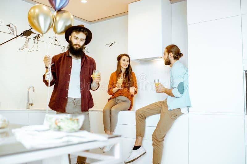 Vänner som hemma firar födelsedag på köket arkivfoto