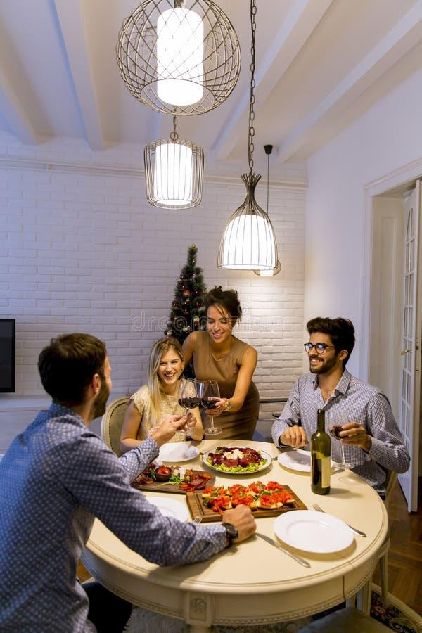 Vänner som hemma firar helgdagsafton för jul eller för nytt år royaltyfri fotografi