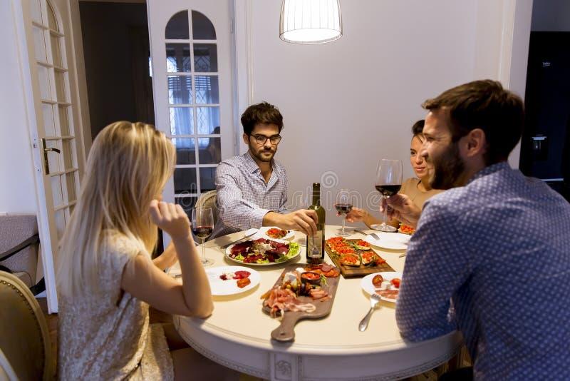 Vänner som hemma firar helgdagsafton för jul eller för nytt år arkivfoto