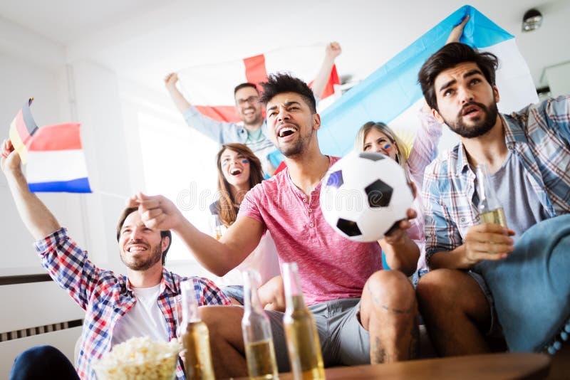 Vänner som hemma håller ögonen på fotbollleken royaltyfri bild