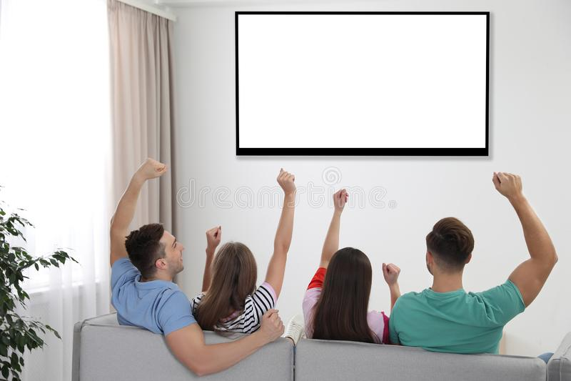 Vänner som hemma håller ögonen på TV på soffan royaltyfri bild