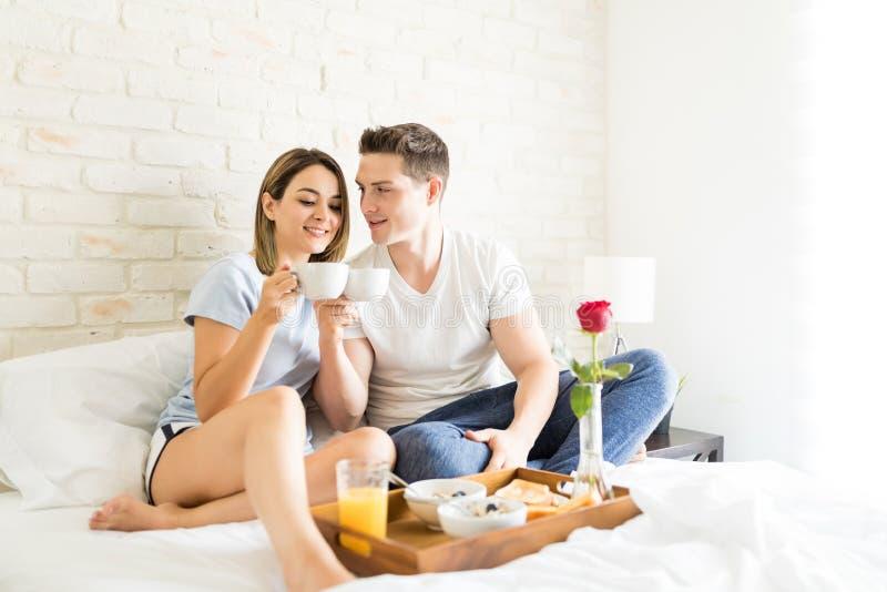 Vänner som hemma klirrar kaffekoppar på säng arkivbilder