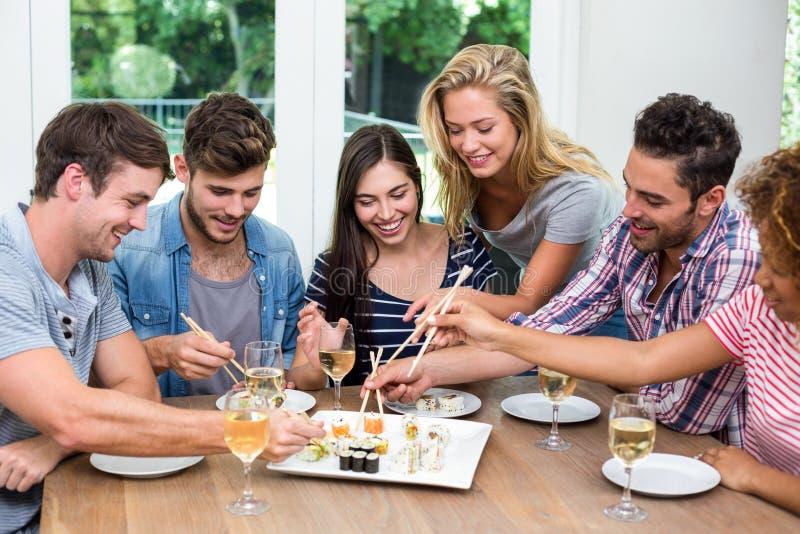 Vänner som hemma tycker om vin och sushi royaltyfri foto