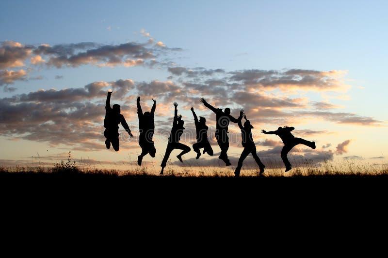 vänner som hoppar silhouettes royaltyfri fotografi