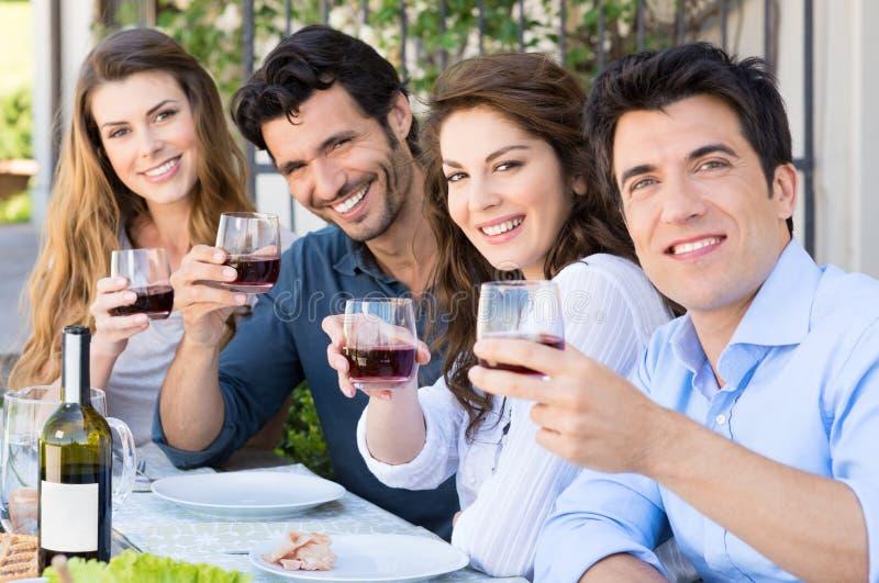 Vänner som hurrar med vinexponeringsglas royaltyfria foton