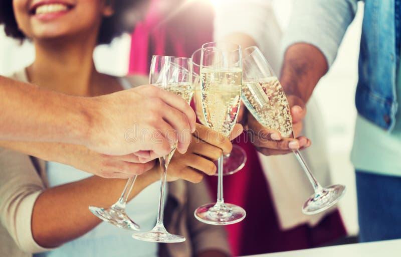 Vänner som klirrar exponeringsglas av champagne på partiet fotografering för bildbyråer