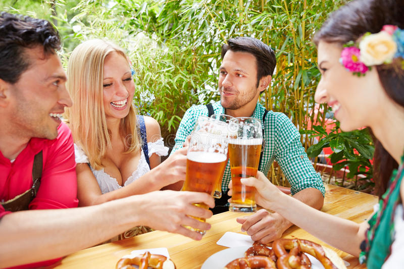 Vänner som klirrar exponeringsglas med öl royaltyfri bild