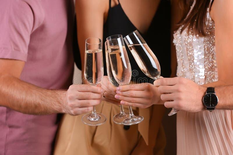 Vänner som klirrar exponeringsglas med champagne, closeup fotografering för bildbyråer