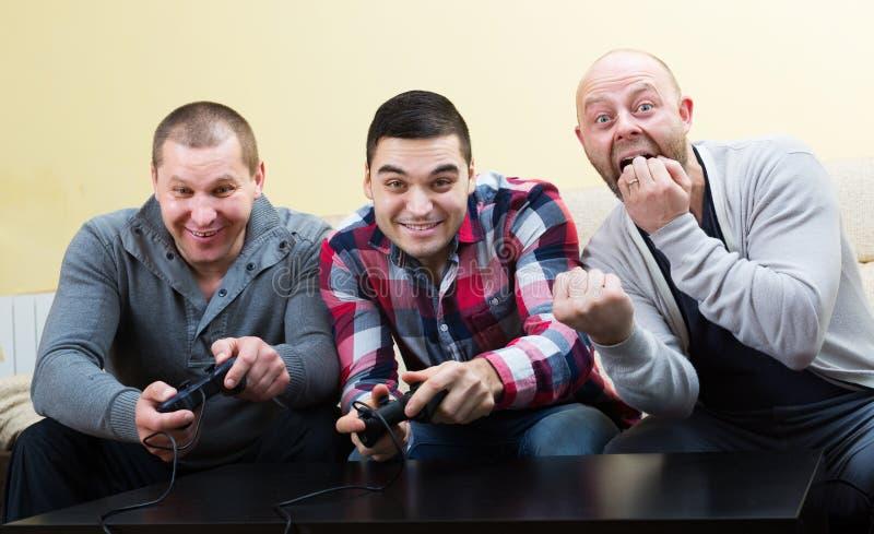 Vänner som kopplar av med videospelet fotografering för bildbyråer