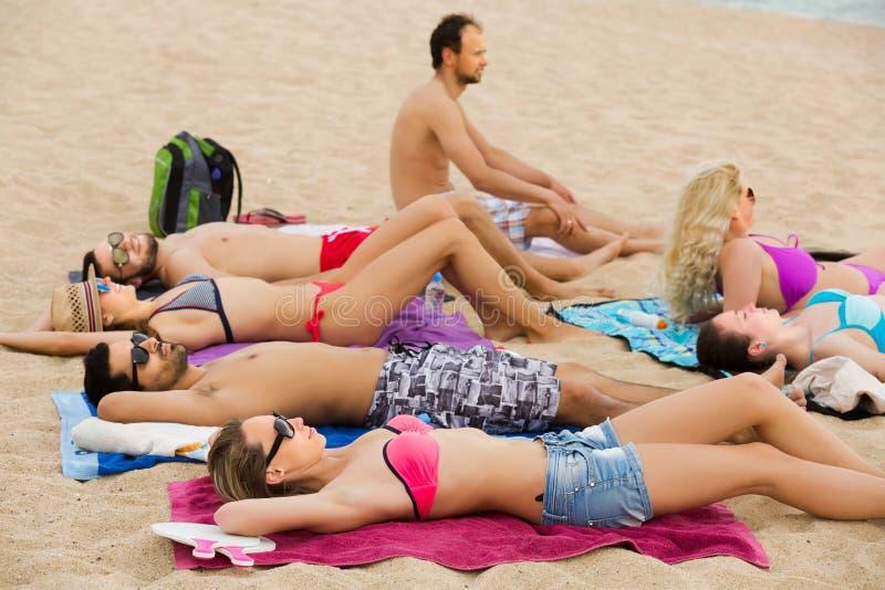 Vänner som kopplar av på den sandiga stranden arkivfoto