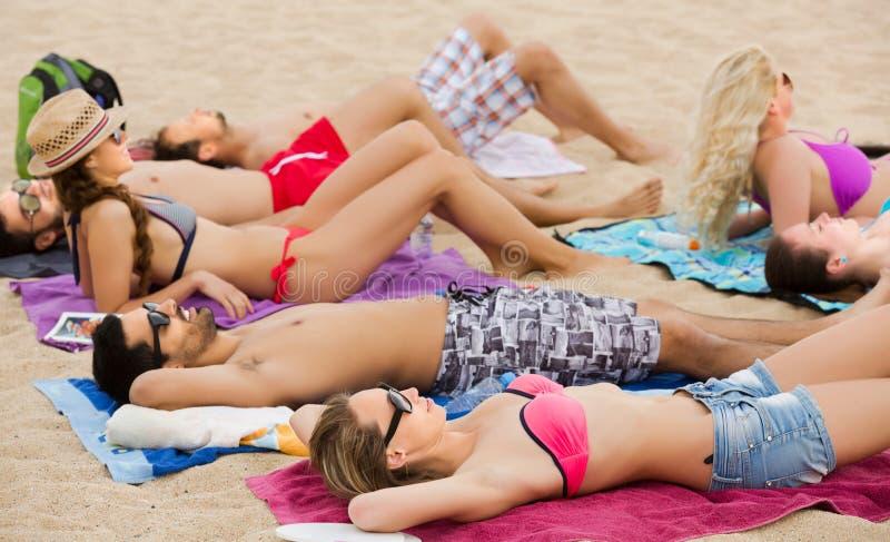 Vänner som kopplar av på den sandiga stranden fotografering för bildbyråer