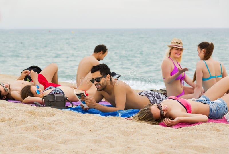 Vänner som kopplar av på den sandiga stranden royaltyfria foton