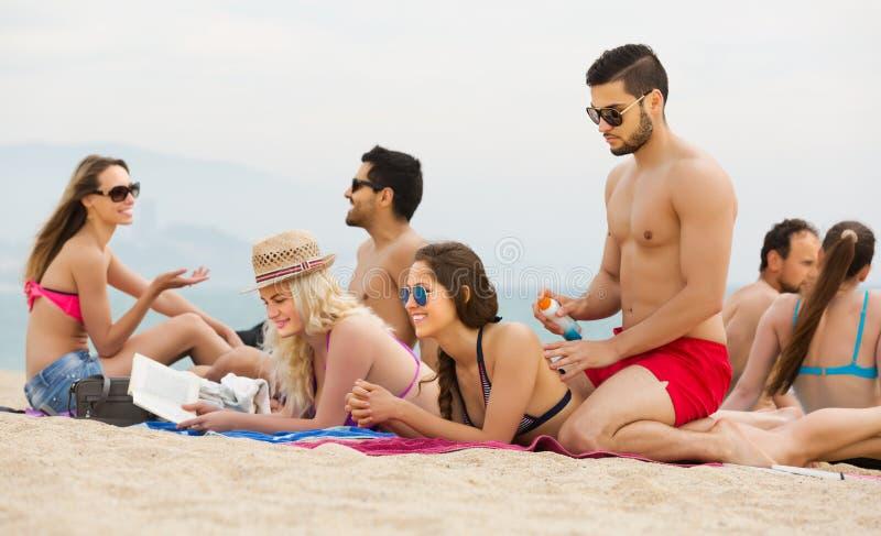 Vänner som kopplar av på den sandiga stranden arkivfoton