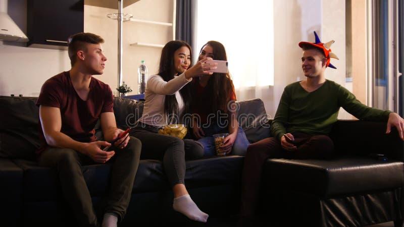 Vänner som kopplar av på helgen Fyra ungdomarsom sitter på soffan och den hållande ögonen på TV:N royaltyfria bilder