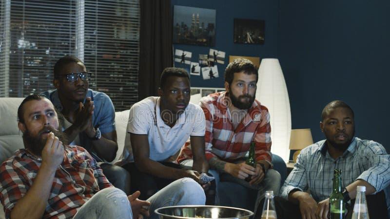 Vänner som kyler på soffan, medan hålla ögonen på leken på TV arkivfoton