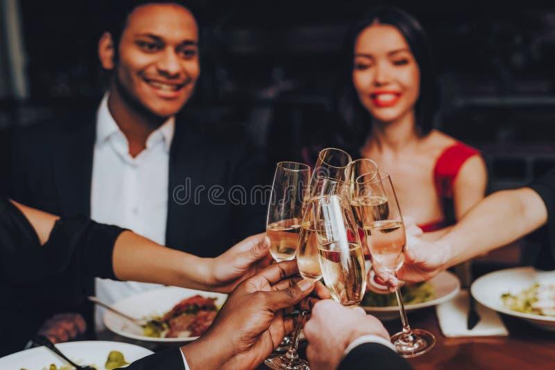 Vänner som kyler ut att tycka om mål i restaurang royaltyfria bilder