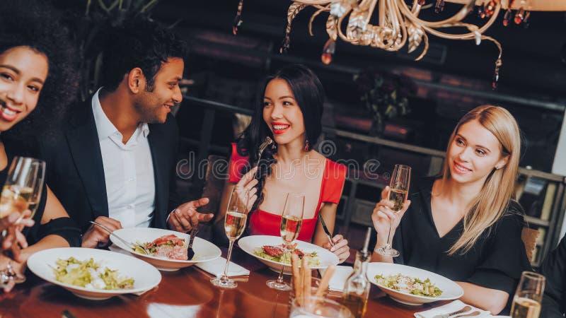 Vänner som kyler ut att tycka om mål i restaurang arkivbilder