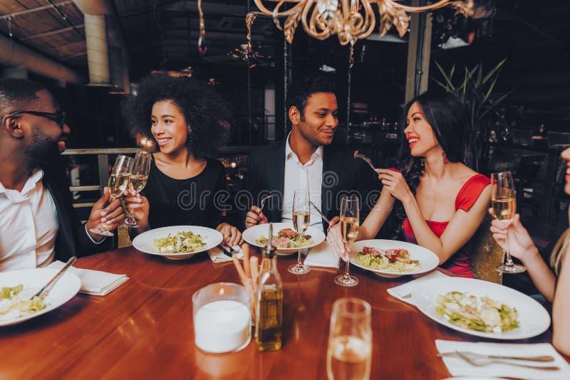 Vänner som kyler ut att tycka om mål i restaurang royaltyfri foto