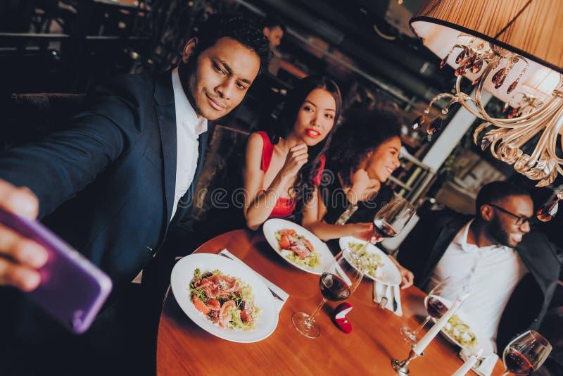 Vänner som kyler ut att tycka om mål i restaurang royaltyfri bild