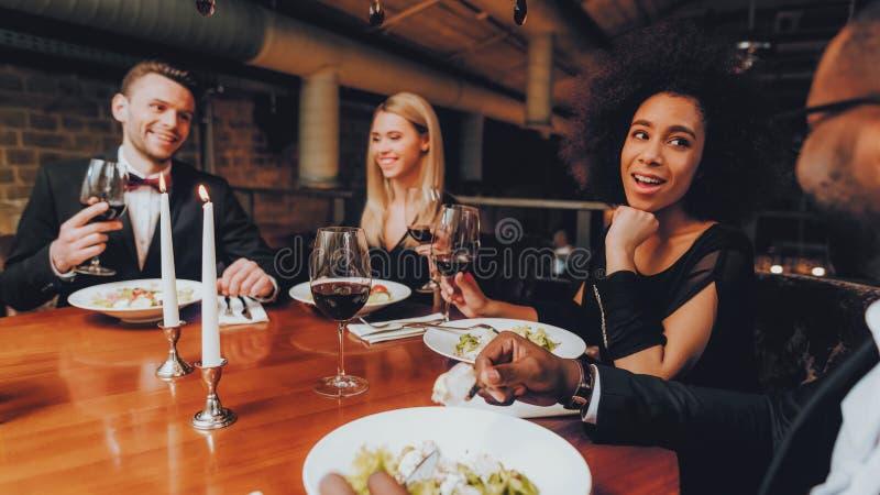 Vänner som kyler ut att tycka om mål i restaurang fotografering för bildbyråer