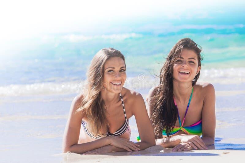Vänner som lägger på sand royaltyfri fotografi