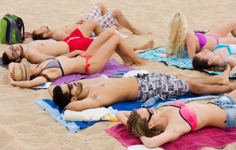 Vänner som lägger på sand på stranden arkivfoto