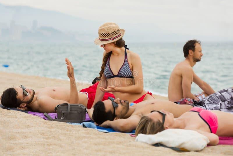 Vänner som lägger på sand på stranden royaltyfri fotografi