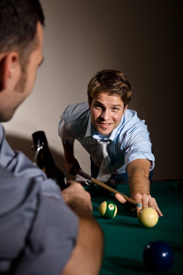 Vänner som leker snookeren på stången royaltyfri foto