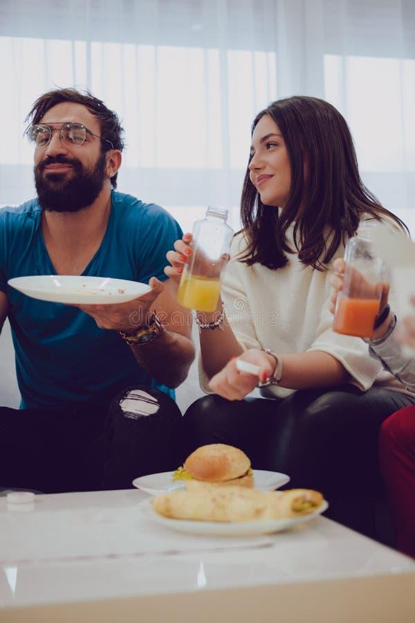 Vänner som ler, medan rymma fruktsafter arkivfoto
