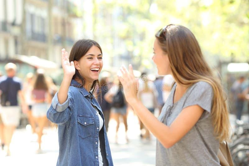 Vänner som möter och hälsar i gatan fotografering för bildbyråer